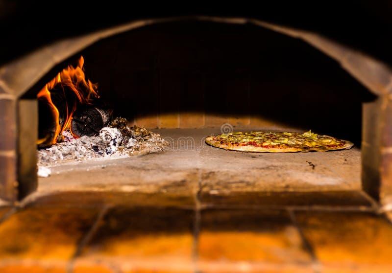 在砖木烤箱的烘烤的比萨与木柴和火焰 烹调的可口比萨It's自创和原始的惯例 它 免版税库存照片