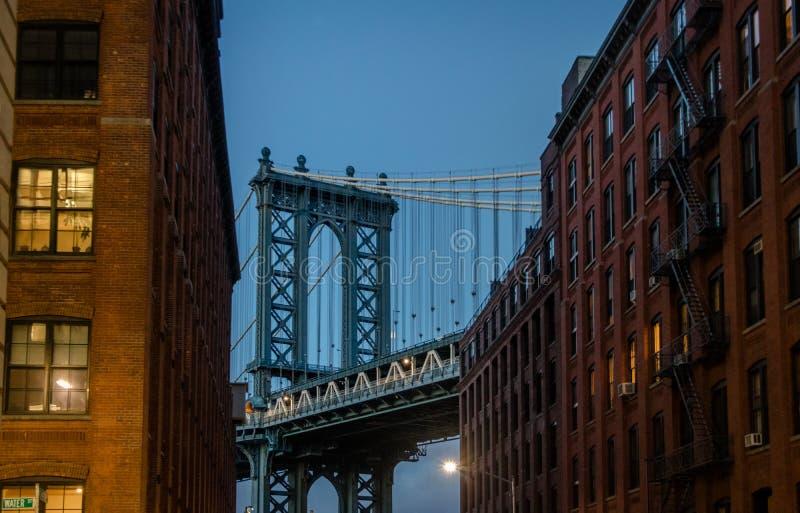 从在砖瓦房之间的Dumbo看见的曼哈顿桥梁在布鲁克林在日落-纽约,美国 库存图片