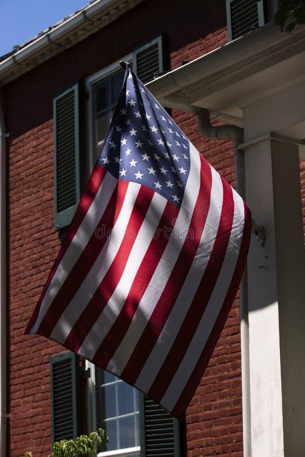 在砖瓦房前面的美国国旗飞行在阿珀维尔弗吉尼亚在福基尔县 免版税库存图片