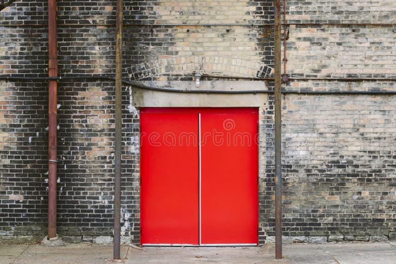 在砖瓦房的红色门 免版税图库摄影