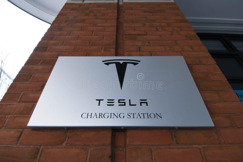 在砖背景的一个特斯拉充电站标志在一家旅馆在波兹毛斯, N H ,美国 免版税库存图片