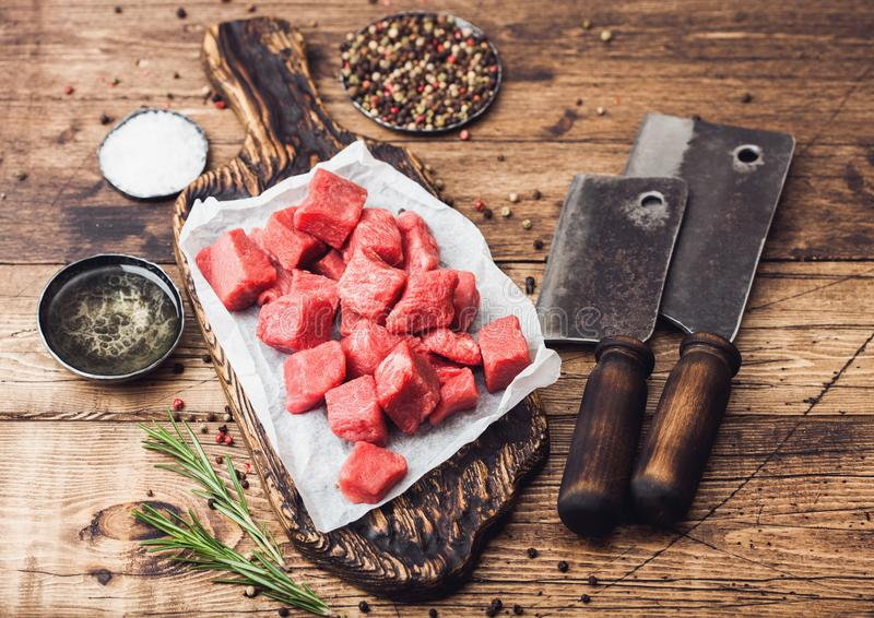 在砧板的未加工的精瘦的切成小方块的砂锅牛肉猪肉牛排有葡萄酒在木背景的肉柴刀的 盐和胡椒与 免版税图库摄影
