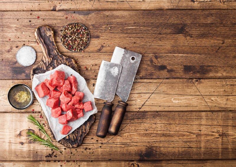 在砧板的未加工的精瘦的切成小方块的砂锅牛肉猪肉牛排有葡萄酒在木背景的肉柴刀的 盐和胡椒与 免版税库存照片