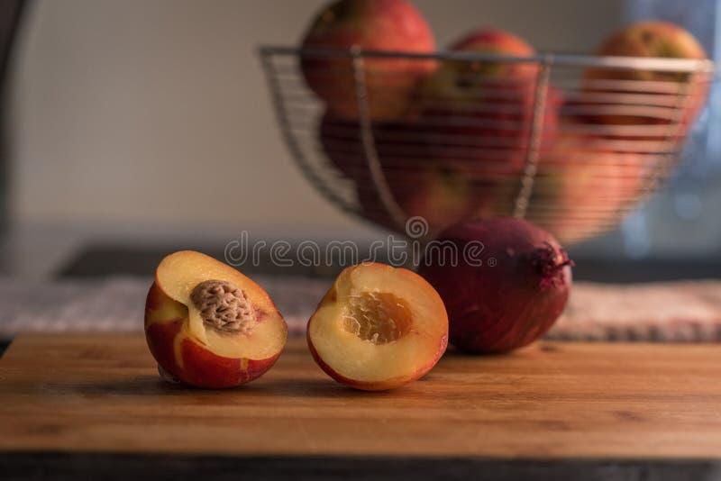 在砧板的油桃一半 免版税库存图片