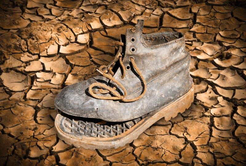 在破裂的地面放弃的老残破的起动-贫穷概念 免版税库存图片