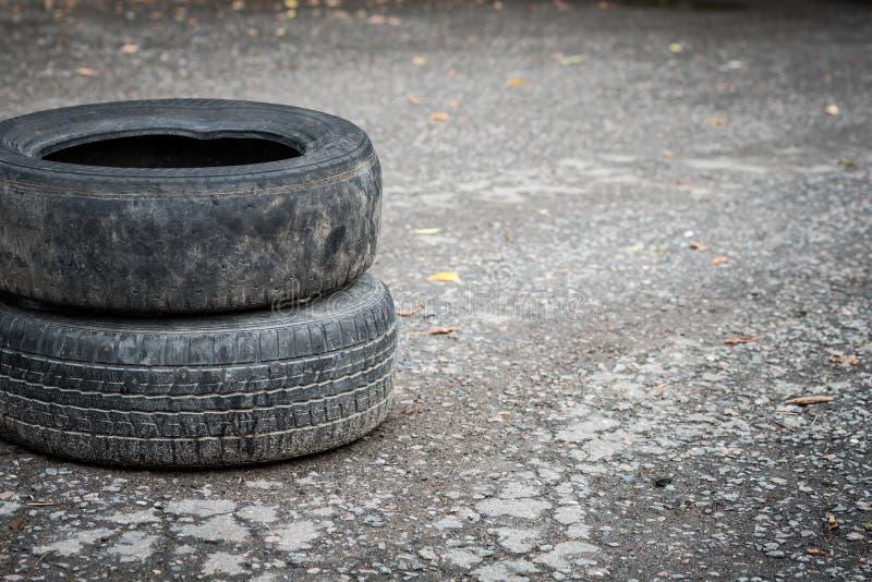 在破裂的沥青的老肮脏的车胎 r 免版税图库摄影