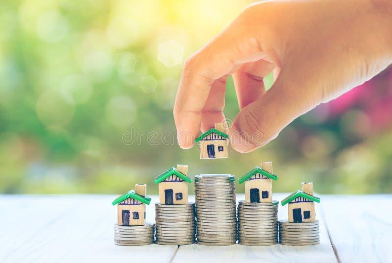 在硬币人` s手安置的议院计划硬币储款金钱买物产梯子的一个家庭概念概念,抵押a 库存照片