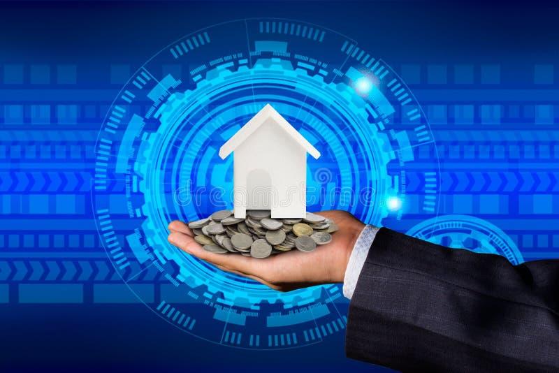 在硬币安置的一个商人在他的手上和一个式样房子的手与硬币的 免版税库存照片