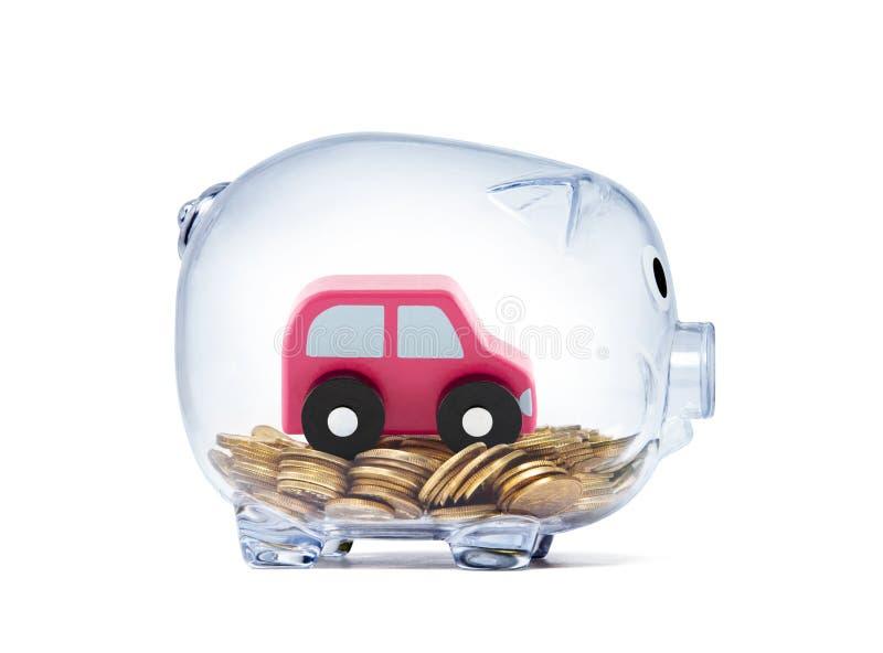 在硬币的汽车玩具在透明存钱罐里面 库存图片