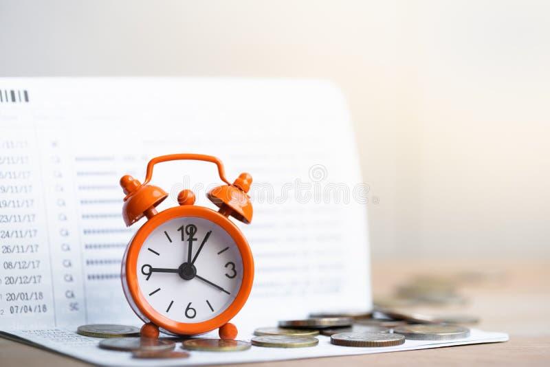 在硬币的闹钟在银行存款簿背景堆积  库存图片