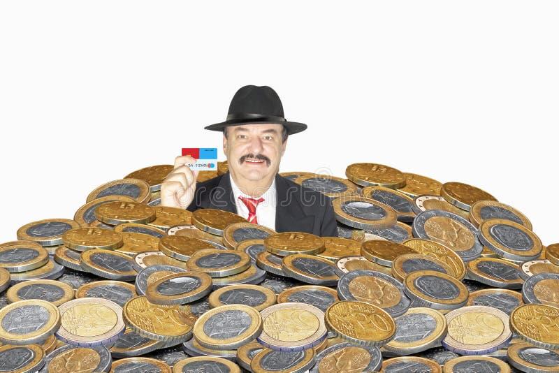 在硬币重压下的商人 库存照片