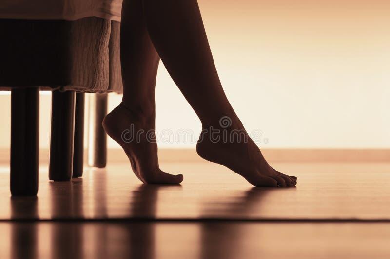 在硬木地板上的女性脚 醒和起来从床的年轻女人早晨 腿和身体剪影  免版税库存图片