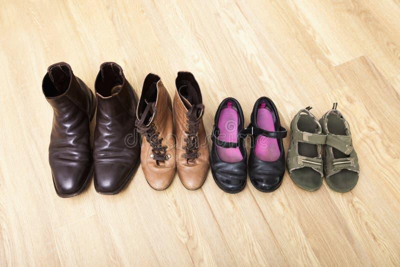 在硬木地板连续安置的家庭鞋子 免版税库存照片