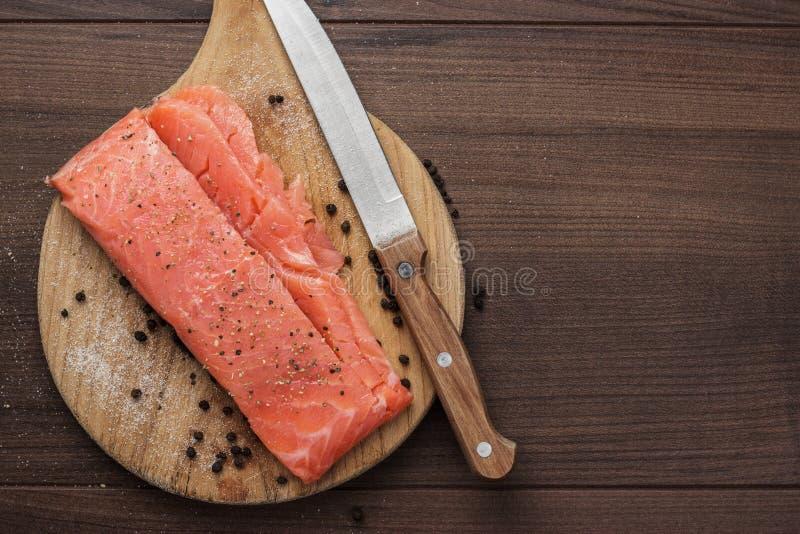 在硬质纤维板的盐味的鳟鱼 库存图片