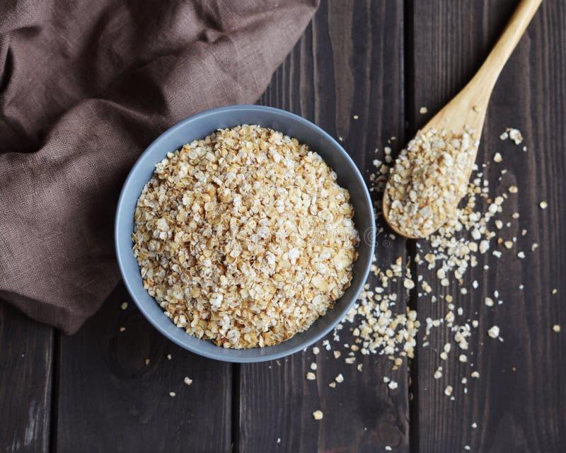在碗和匙子的燕麦片在黑暗的木桌,顶视图上 免版税图库摄影
