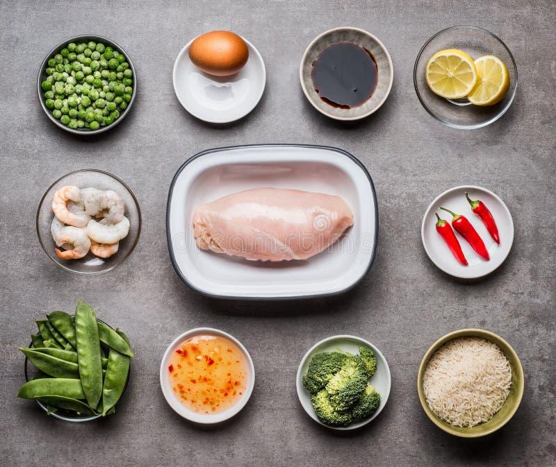 在碗和各种各样的健康烹调成份的未加工的鸡胸脯内圆角在石背景,顶视图的鲜美饮食膳食的 库存图片