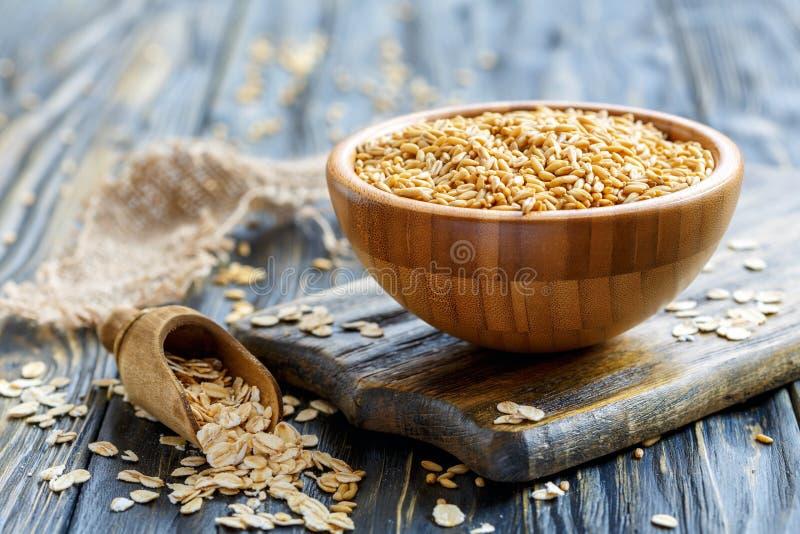 在碗和燕麦剥落的整个燕麦在一个木瓢 免版税库存图片