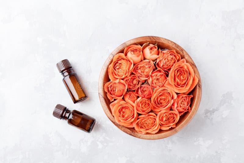 在碗和精油瓶的罗斯花在石台式视图 温泉,芳香疗法,健康,秀丽背景 库存照片