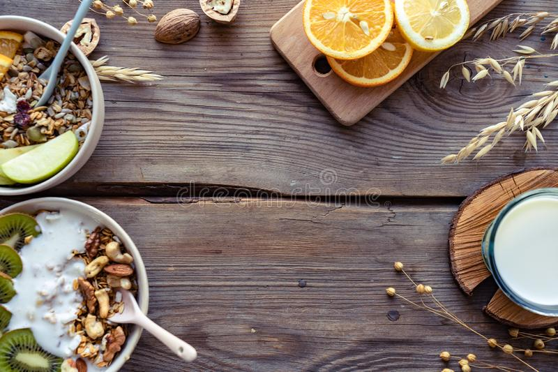 在碗牛奶的健康早餐格兰诺拉麦片食物水果酸牛奶在棕色木桌上 图库摄影
