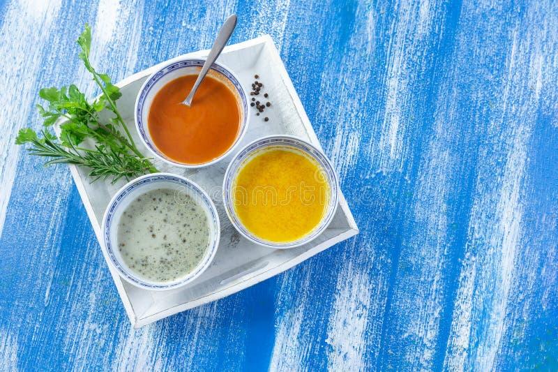在碗的五颜六色的绿色,黄色和红色辣调味汁在蓝色木被绘的板条隔绝的一块白色板材 免版税库存图片