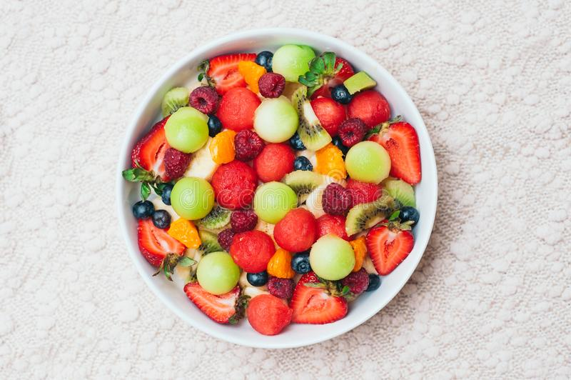在碗的健康新鲜水果沙拉 切片草莓,莓,猕猴桃,蜜桔,在板材的蓝莓 可口果子 免版税库存图片