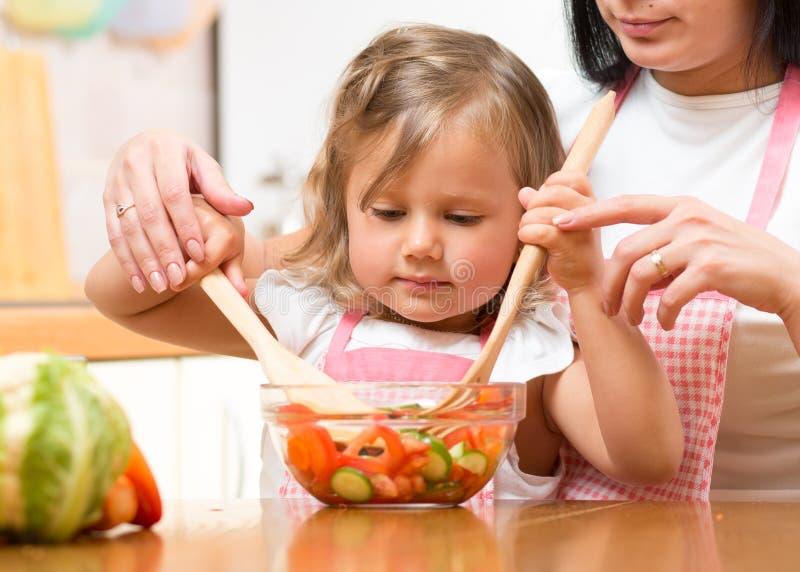 在碗的儿童女孩混合的沙拉在母亲帮助下在厨房里 免版税库存照片