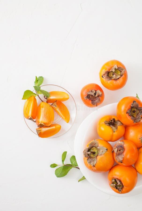 在碗的切好的成熟柿子在白色桌上 库存图片