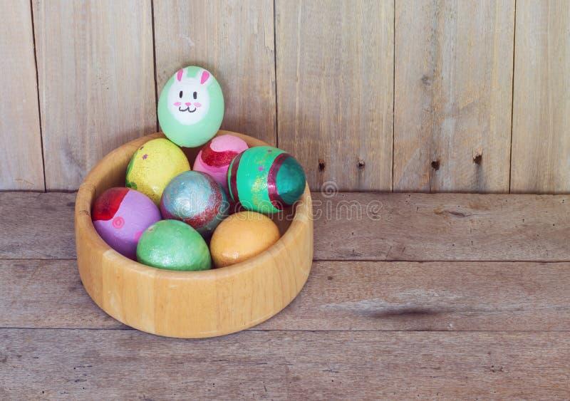 在碗的复活节彩蛋木在木背景 免版税库存图片