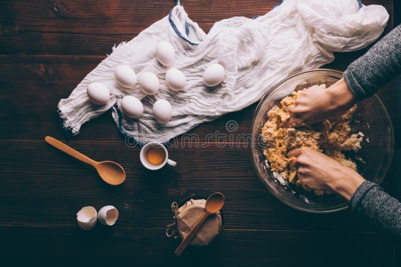 在碗的妇女的手揉的面团在鸡蛋旁边 免版税库存照片