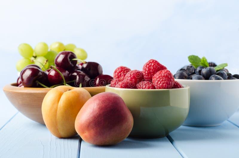 在碗的新鲜水果选择在浅兰的木Planked表上 库存照片