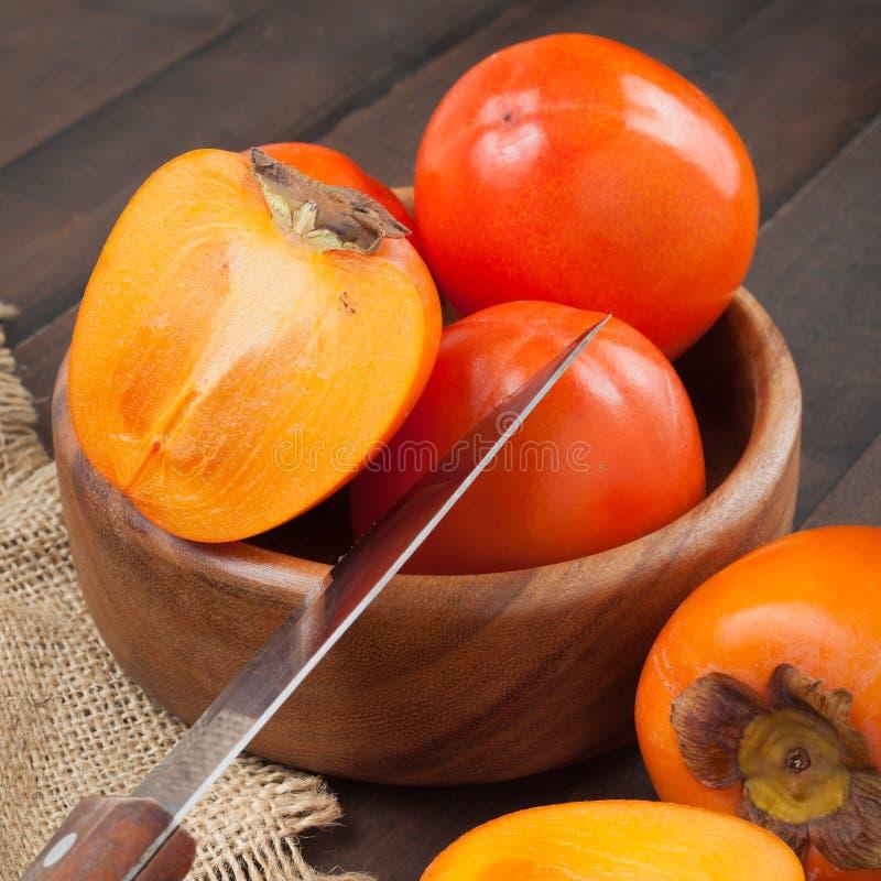 在碗的柿子有在桌上的厨刀的 免版税库存照片