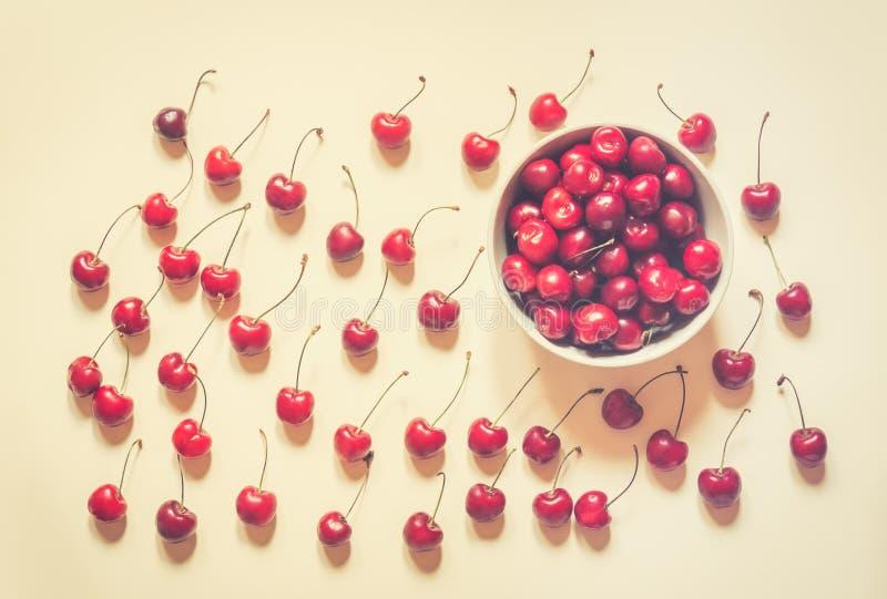 在碗的樱桃和在米黄背景临近 库存图片