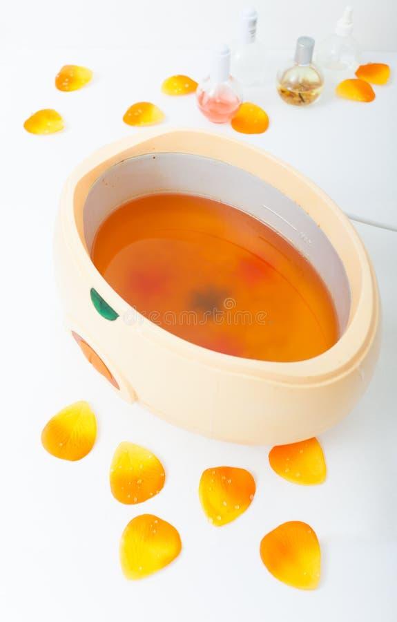 在碗的橙色parrafin蜡。在秀丽温泉沙龙的修指甲。 免版税库存照片