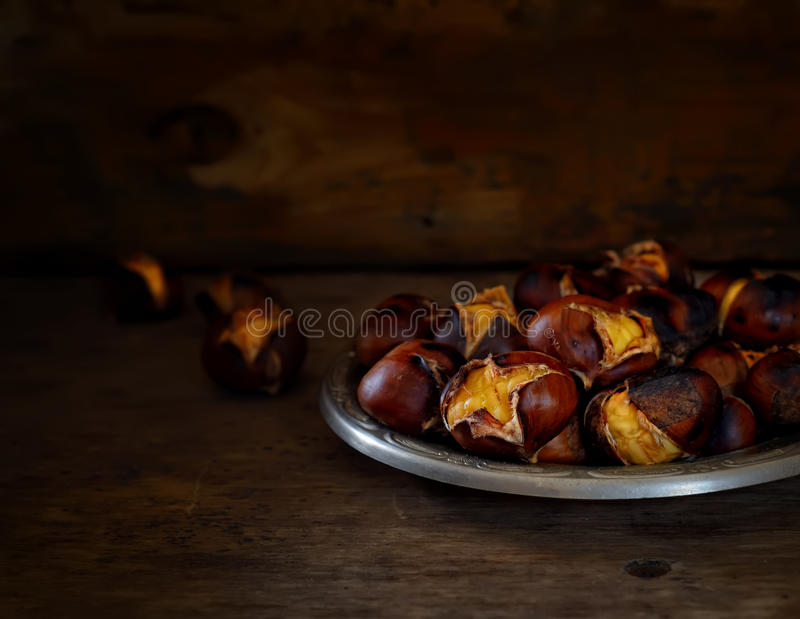 在碗的烤栗子在黑暗的木背景 库存图片