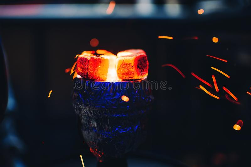 在碗的热的煤炭水烟筒加热与假日和抽烟的飞行红色火花 库存照片