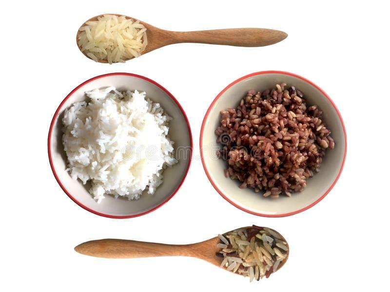在碗的煮沸的米用在白色背景在茉莉花和riceberry米顶视图之间隔绝的木匙子的未加工的谷物米 库存图片