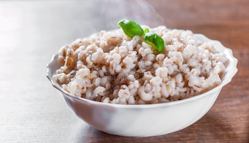 在碗的煮熟的大麦米在一张木桌上 免版税库存照片