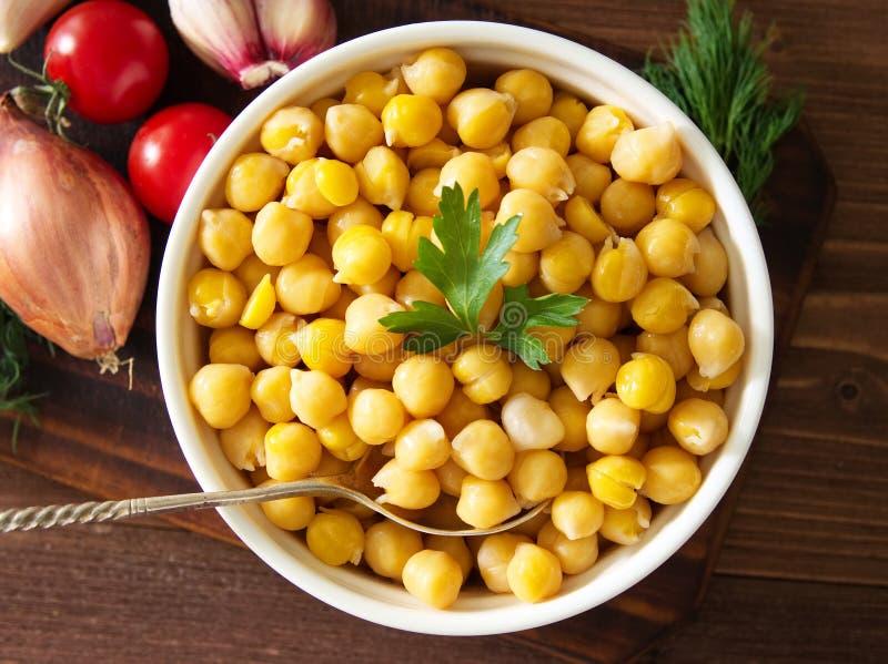 在碗的煮熟的鸡豆在黑暗的木桌上 中东顶视图健康,素食滋补蛋白质食物  库存照片