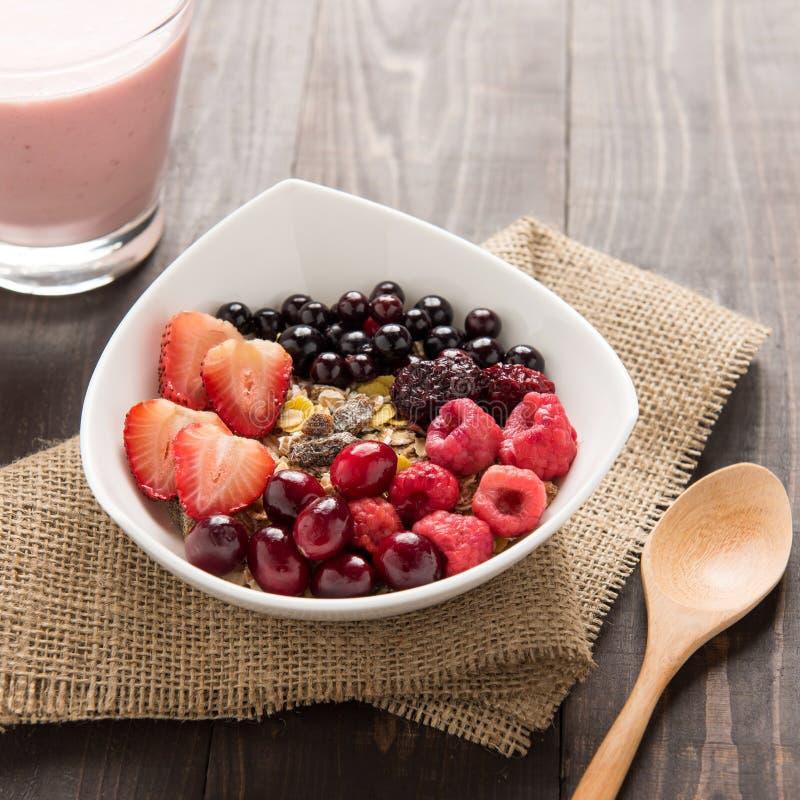 在碗的燕麦粥冠上了用新鲜的蓝莓,蔓越桔, stra 图库摄影