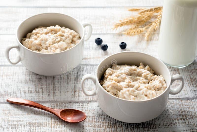 在碗的燕麦粥粥在白色桌,健康饮食早餐上 免版税库存照片
