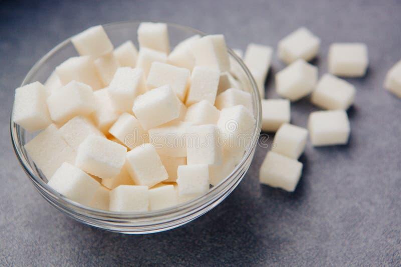 在碗的白糖立方体在灰色背景 免版税库存照片
