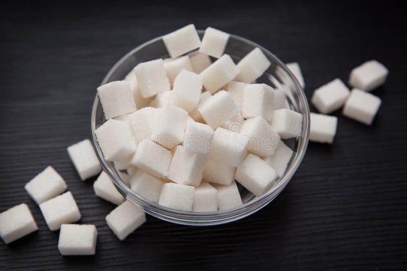 在碗的糖在黑背景 库存图片