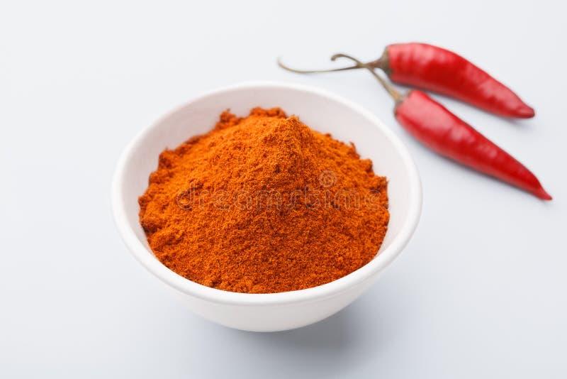 在碗的红色冷颤的粉末在白色背景 免版税库存照片