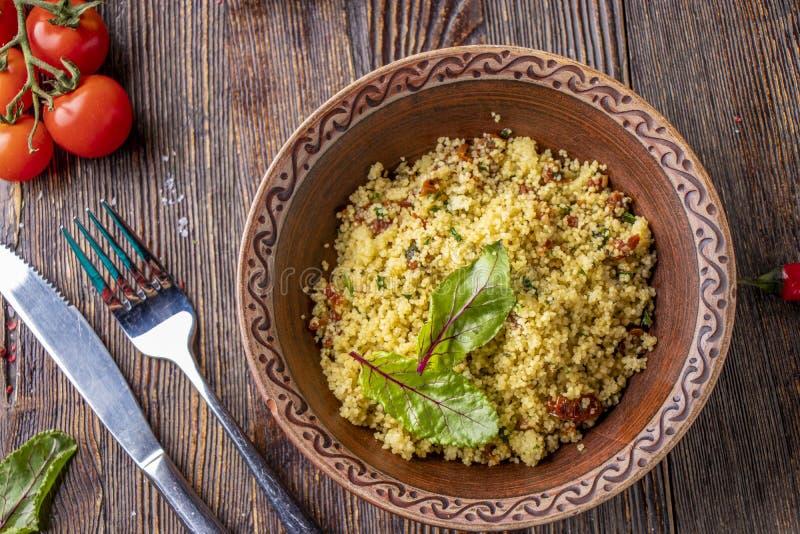 在碗的蒸丸子有橄榄油和干蕃茄的在木背景,东方烹调,水平的照片 库存照片