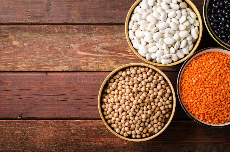 在碗的被分类的豆用红色小扁豆、鸡豆和扁豆在木背景 图库摄影