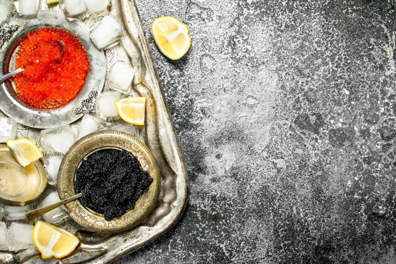 在碗的黑和红色鱼子酱在老盘子 免版税库存照片