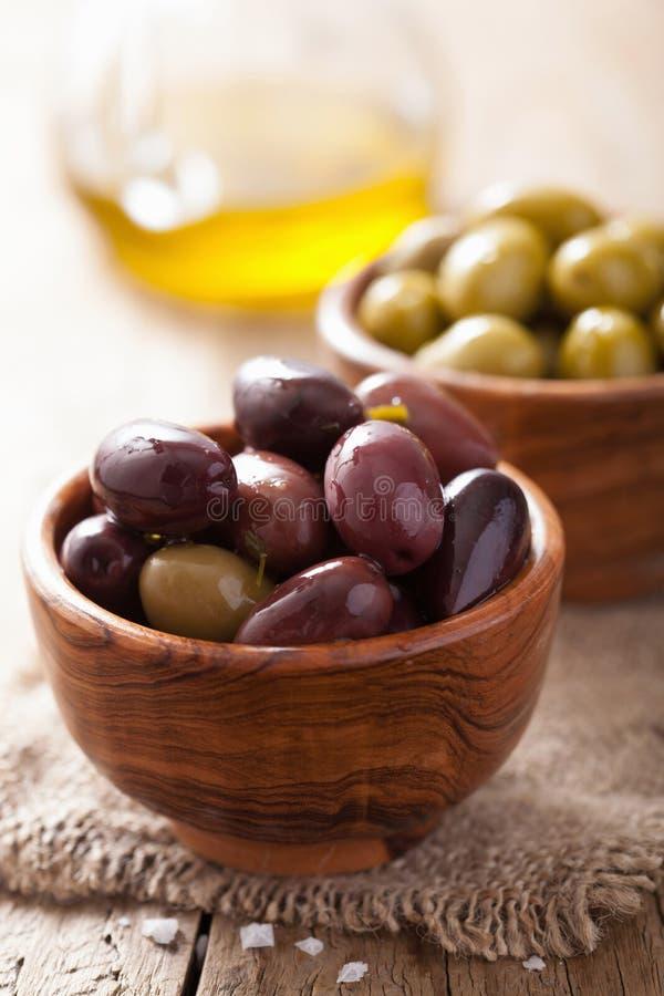 在碗的黑和绿色用卤汁泡的橄榄 免版税库存照片