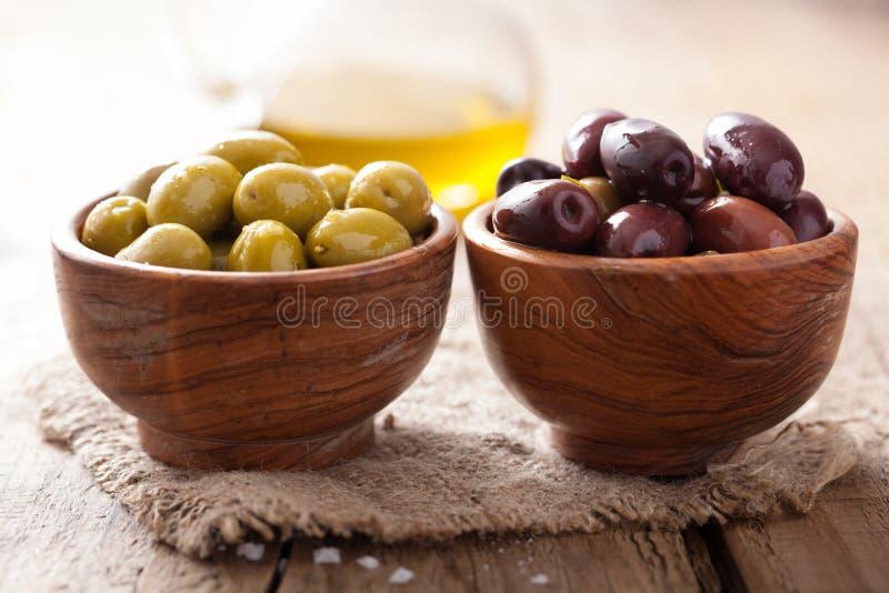 在碗的黑和绿色用卤汁泡的橄榄 库存照片
