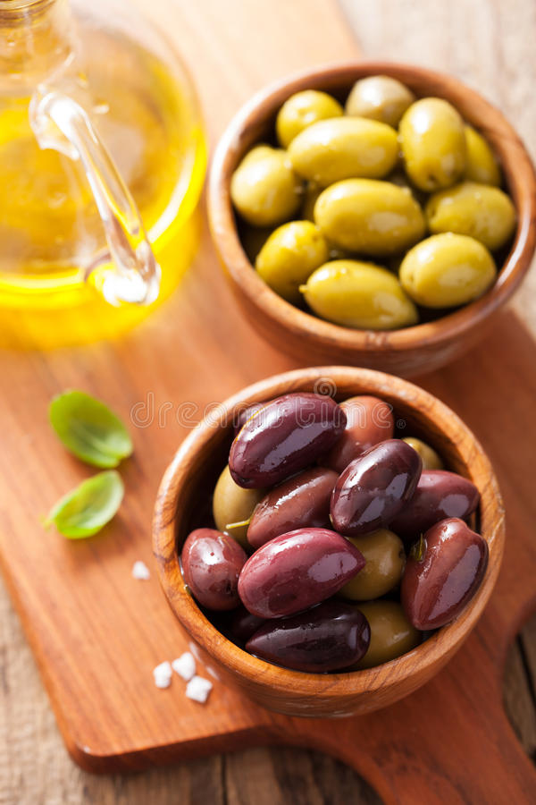 在碗的黑和绿色用卤汁泡的橄榄 免版税库存图片