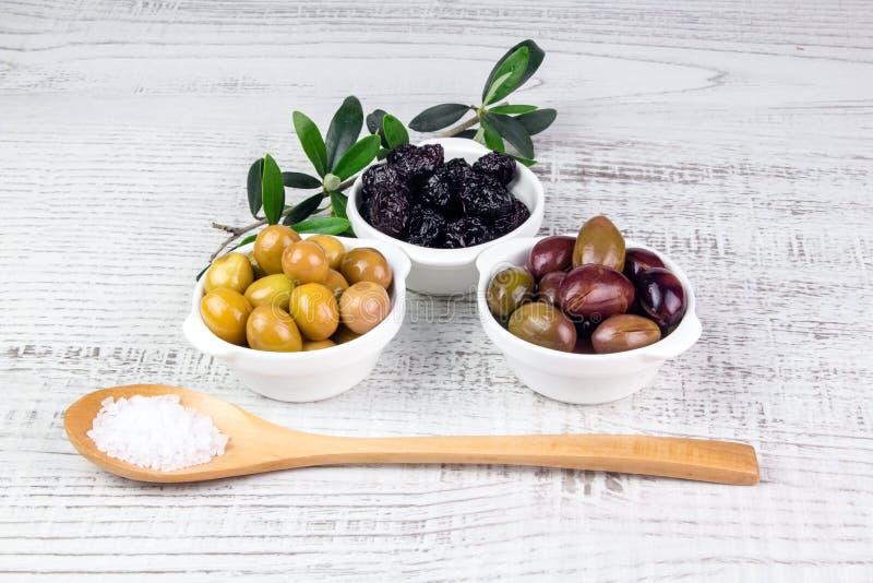 在碗的绿色,黑,桃红色橄榄和一把木匙子 免版税图库摄影